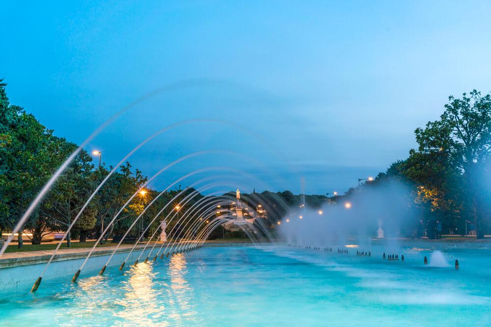 Placha s vodou, do ktorej strieka voda, efekt fontány, osvetlená modrýo-tyrkysovým svetlom